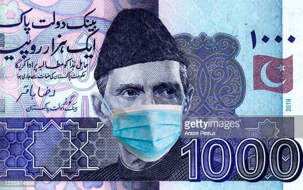 pakistan quarantine, 1000 rupees banknote with medical mask. the concept of epidemic and protection against coronavrius. - pakistan stock pictures, royalty-free photos & images