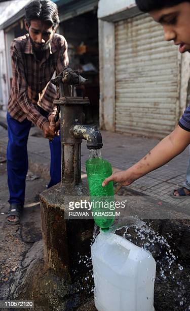 Pakistan residents fill up a container with drinking water from a handpump in an impoverished neighbourhood of Karachi on March 22 on World Water Day...