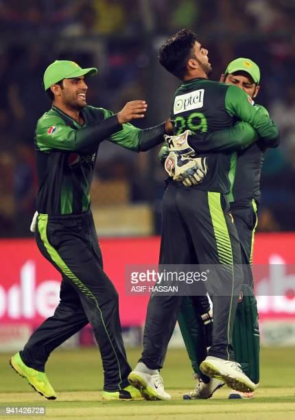 Pakistan spinner Shadab Khan celebrates with team captain Sarfraz Ahmed and teammate Fakhar Zaman after dismissal of West Indies batsman Marlon...