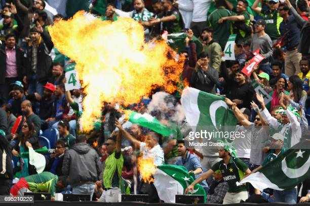 Pakistan supporters show their colours as pyrotechnics are lit at the fall of a wicket during the ICC Champions Trophy match between Sri Lanka and...