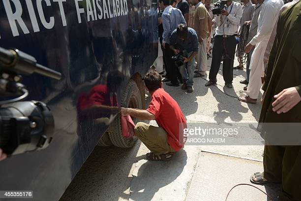 Pakistan Tehreek-e-Insaf worker deflates the tyre of a police prison van carrying arrested workers to prevent them from leaving the court area in...