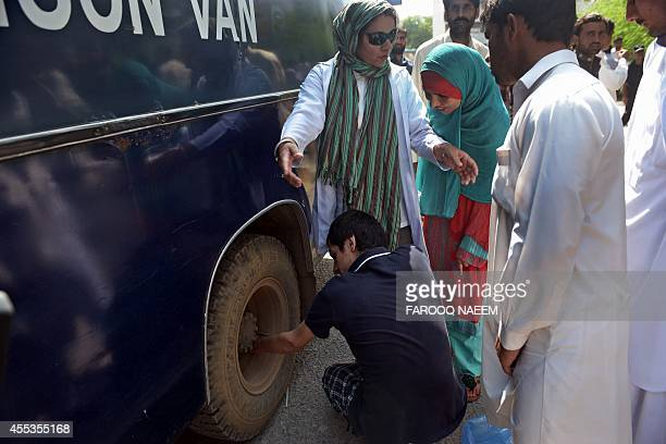 Pakistan TehreekeInsaf workers deflate the tyre of a police prison van carrying arrested workers to prevent them from leaving the court area in...