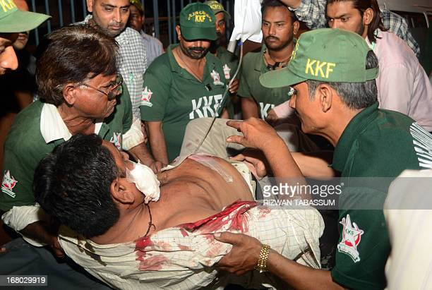 Pakistan volunteers shift an injured blast victim to a hospital in Karachi on May 4 2013 after a bombing on the secular Muttahida Qaumi Movement...