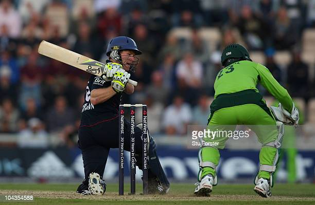 Pakistan wicketkeeper Kamran Akmal looks on as England batsman Eoin Morgan sweeps a ball towards the boundary during the 5th NatWest ODI between...