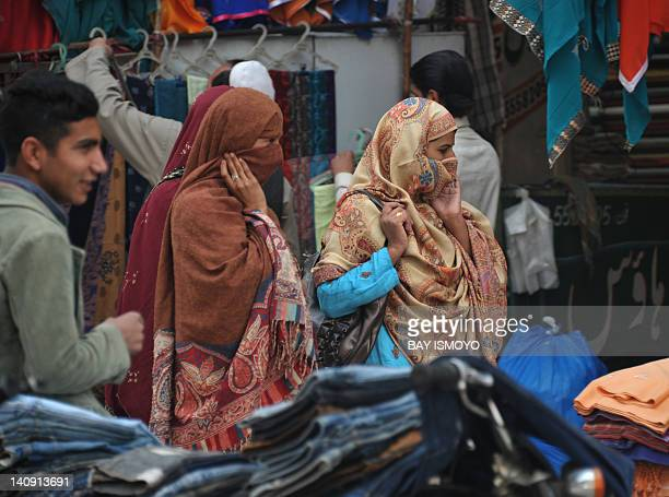 Pakistan women walk past clothes vendors in a street market in Rawalpindi on March 8 2012The UN agency mandated to promote gender equality announced...
