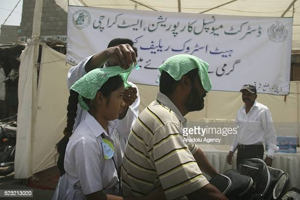 People puts a wet towel on the head of citizens during a heat wave in Karachi Pakistan on April 22 2016