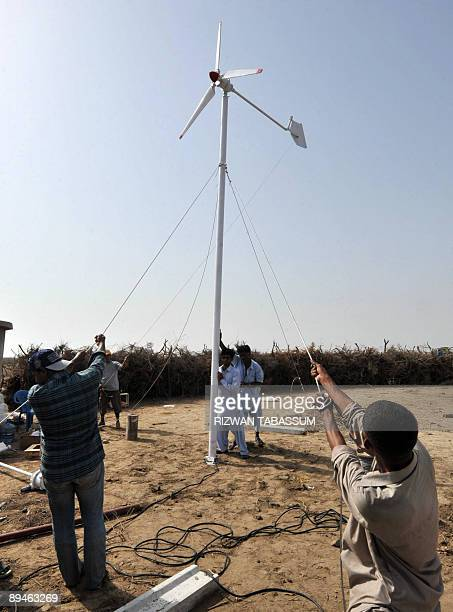 Pakistaneconomyenergy BY HASAN MANSOOR In a picture taken on May 3 2009 Pakistani technicians install a wind turbine on the subtropical island of...