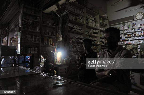 PakistanenergyelectricityeconomyFOCUS by Damon Wake Pakistani vendors wait for customers in a dark shop during a power cut in Islamabad on July 31...