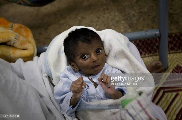 Pakistani abandoned newborn Iqbal who was found in an Edhi cradle gestures at The Edhi Orphanage in Karachi on February 22 2010 Bilquis Edhi a...