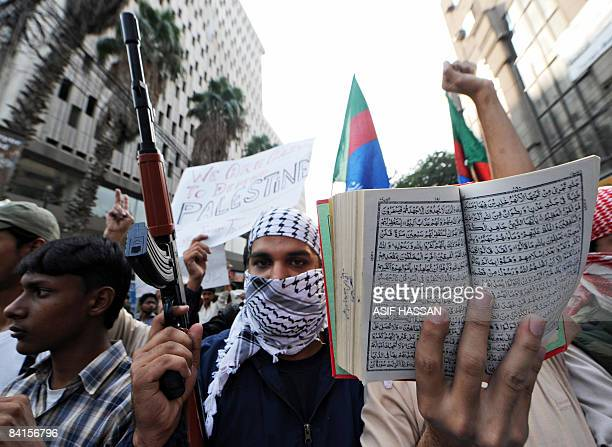 A Pakistani activist of Islami JamiateTulaba a student wing of fundamentalist party JamaatiIslami carries a toy gun and a copy of the Koran during a...