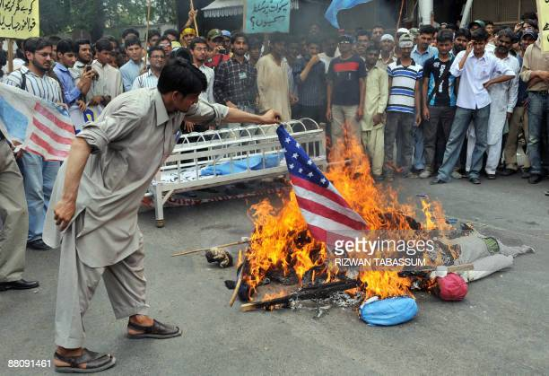 A Pakistani activist of Islami JamiateTulaba a student wing of fundamentalist party JamaatiIslami torches a US flag along with burning effigies of US...