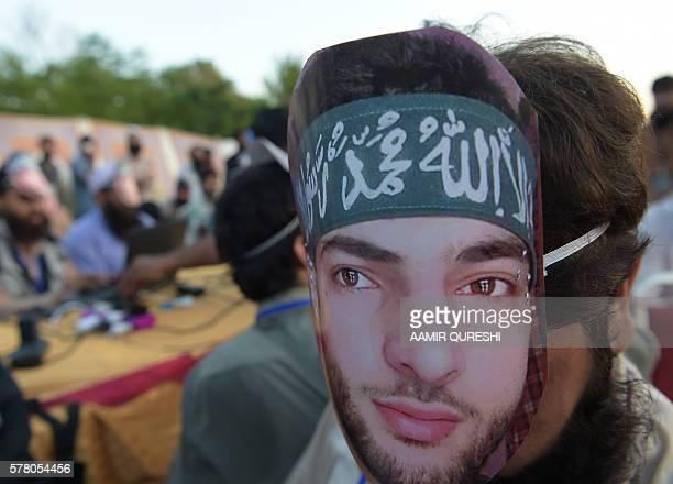 A Pakistani activist of the hardline organisation JamaatudDawa wears a mask of slain popular Indian Kashmiri rebel leader Burhan Wani at a rally to...