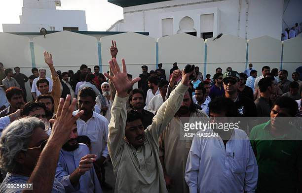 Pakistani activists and supporters chant slogans during the funeral ceremony of Tehreek-e-Insaf leader Zohra Hussain in Karachi on May 19, 2013....