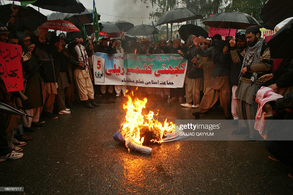 Pakistani activists from Jamaat e Islami Kashmir gather around burning effigy of Indian Prime Minister Manmohan Singh to mark a Kashmir Solidarity Day rally in Muzaffarabad, the capital of Pakistan-administered Kashmir on February 5, 2013. Pakistan observed Kashmir Solidarity Day on February 5, to denounce Indian rule in the disputed Himalayan region claimed in whole by both countries. AFP PHOTO/Sajjad QAYYUM