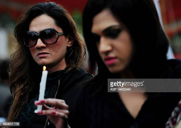 Pakistani activists from the Gender Interactive Alliance hold candles as they take part in a protest in Karachi on December 18 against the attack by...