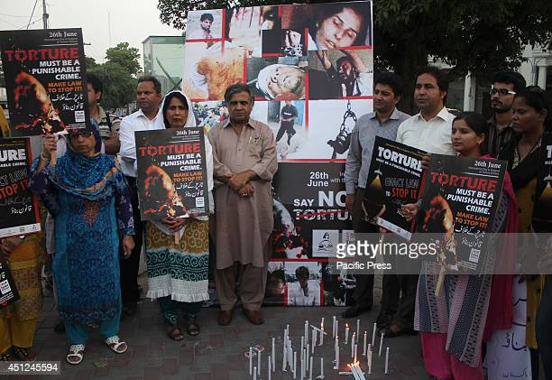 Pakistani activists hold placards and light candles for the victims of torture in Lahore during the eve of International Day in Support of the...