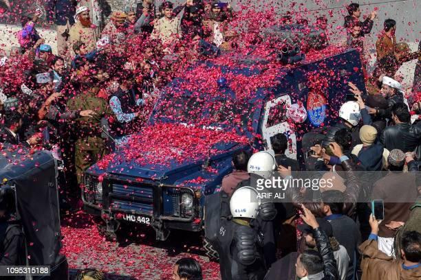 Pakistani activists of TehreekLabaik Pakistan party throw rose petals over an armoured police vehicle carrying their leader Khadim Hussain Rizvi as...