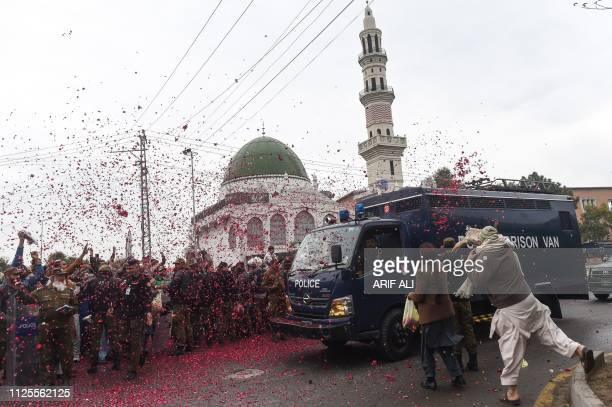 TOPSHOT Pakistani activists of TehreekLabaik Pakistan party throw rose petals over a police van carrying the leader Khadim Hussain Rizvi as he...