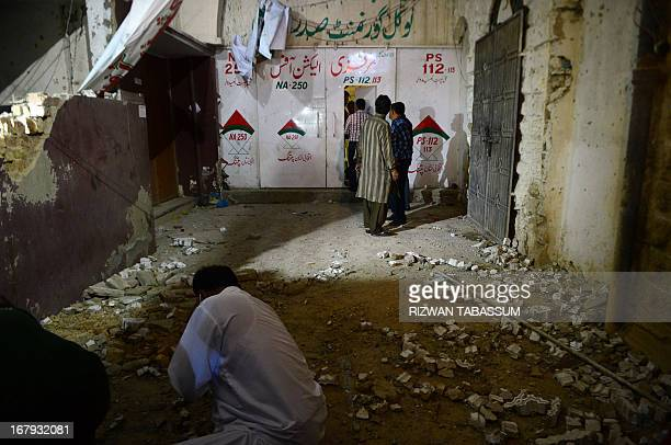 Pakistani activists of the secular Muttahida Qaumi Movement party examine a damaged office after a bomb explosion in Karachi on May 2 2013 The...