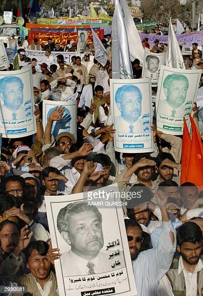 Pakistani activists of the six party Islamic alliance Muttahida MajliseAmal party display portraits of Pakistan's disgraced nuclear scientist Dr...