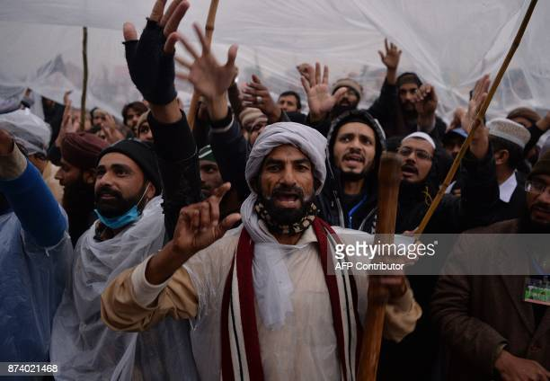 Pakistani activists of the TehreekiLabaik Yah Rasool Allah Pakistan religious group shout slogans from a flyover of a blocked highway during a week...