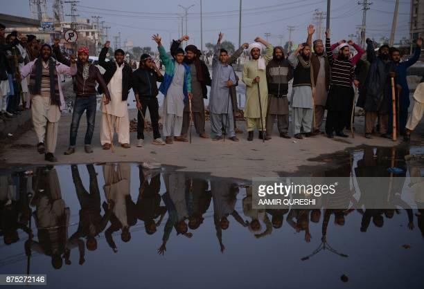 Pakistani activists of the TehreekiLabaik Yah Rasool Allah Pakistan religious group hold bamboos and steel rods as they shout slogans on a blocked...
