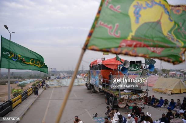 Pakistani activists of the TehreekiLabaik Yah Rasool Allah Pakistan religious group offer Friday prayers on a blocked flyover bridge during a protest...