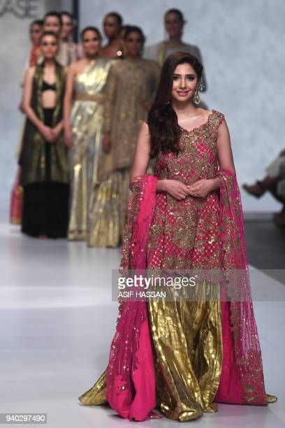 Pakistani actress and model Mahira Khan presents a creation by Pakistani designer Umar Sayeed on the final day of the 'Hum Showcase' Fashion Week in...