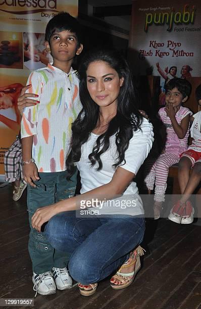 Pakistani actress Veena Malik poses with her newlyadopted Indian girl Payal Kambale during a press event with the Sahara Charitable NGO in Mumbai on...