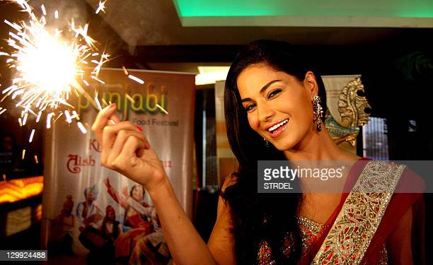 Pakistani actress Veena Malik poses with sparklers during a press event ahead of Diwali in Mumbai on October 22 2011 AFP PHOTO/STR