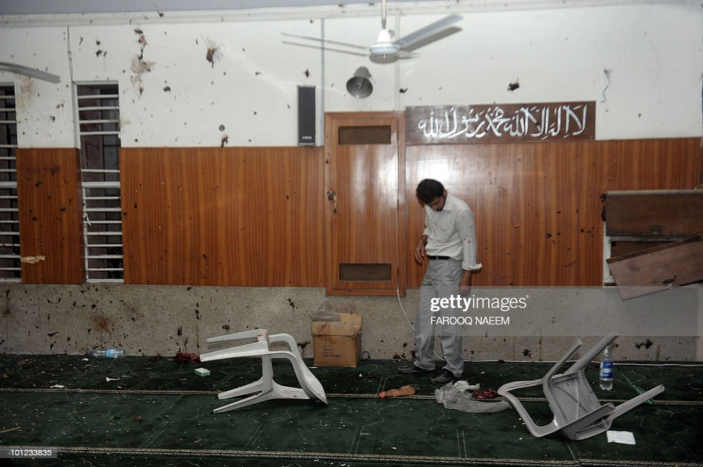 A Pakistani Ahmadi community member inspects the suicide attack site at his mosque in Lahore on May 28, 2010. Gunmen wearing suicide vests stormed two Pakistani mosques firing guns, throwing grenades and taking hostages bringing carnage to Friday prayers and killing around 80 people. AFP PHOTO/Farooq NAEEM