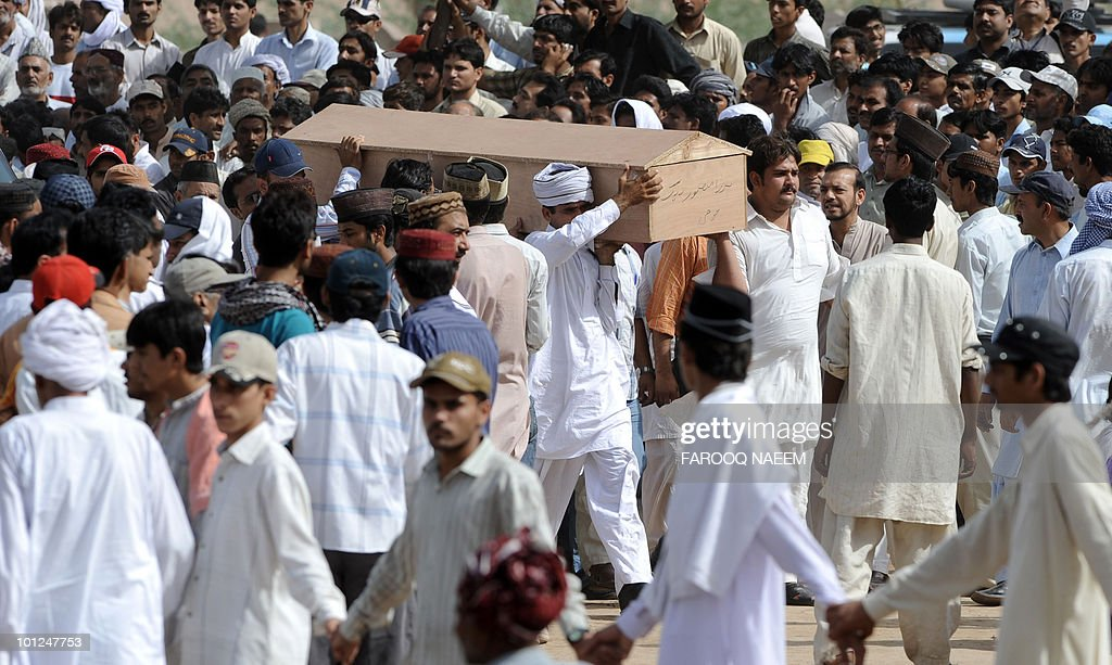 Pakistani Ahmadi community members carry a coffin of a victim during a funeral ceremony at Rabwah, the headquarters of the Ahmadis in Chenab Nagar on May 29, 2010. Gunmen wearing suicide vests stormed two Pakistani mosques belonging to a minority sect in Lahore, bringing carnage to May 28 prayers and killing around 80 people. Squads of militants burst into prayer halls firing guns, throwing grenades and taking hostages in the deadliest attack on the city of eight million, which has been increasingly hit by Taliban and Al-Qaeda-linked violence.