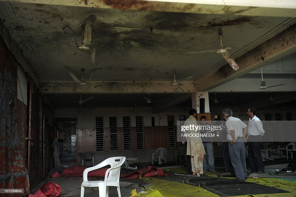 Pakistani Ahmadi community members gather at their mosque after a suicide attack earlier on May 28, 2010 in Lahore. Gunmen wearing suicide vests stormed two Pakistani mosques firing guns, throwing grenades and taking hostages bringing carnage to Friday prayers and killing around 80 people. AFP PHOTO/Farooq NAEEM