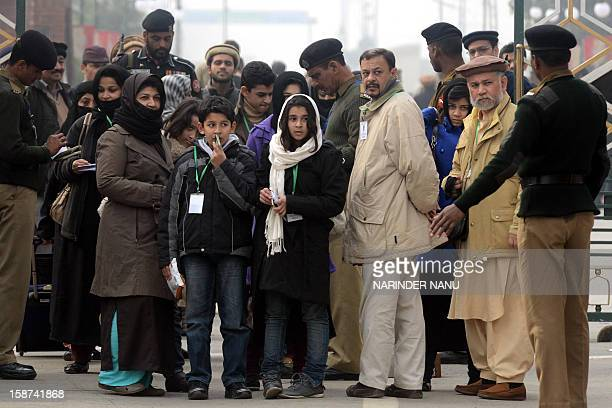 Pakistani Ahmadiyya Muslims wait as their documents are checked by officials at The IndiaPakistan Wagah Border Post on December 27 2012 Thousands of...