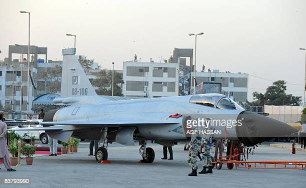 Pakistani airforce personals stand near the JF 17 Thunder aircraft in Karachi on November 23 2008 during preparation for the IDEAS2008 exhibition...