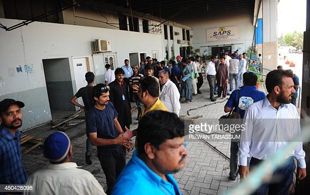 Pakistani airport personnel are pictured outside a burnt storage facility at the Jinnah International Airport in Karachi on June 11 2014 Uzbek...