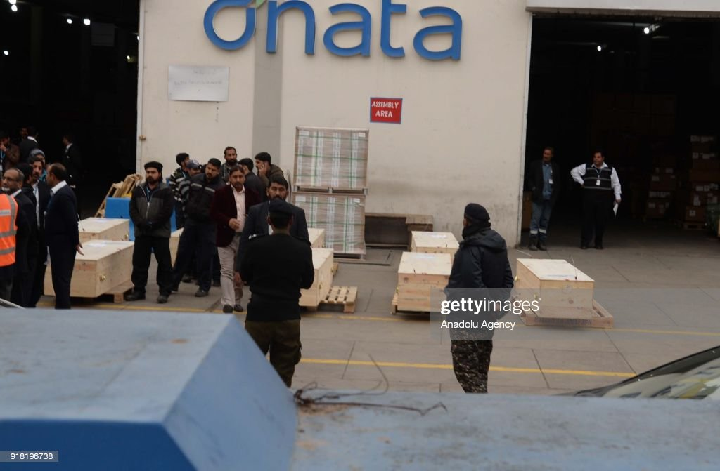 Pakistani airport security officials stand beside the bodies of Pakistani refugees who lost their lives after a boat sank in Libya following their...