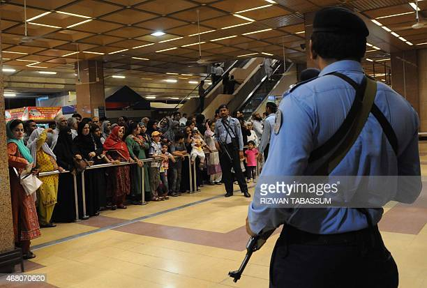 Pakistani Airports Security Force personnels stand guard as relatives of evacuated from Yemen wait in Jinnah International Airport in Karachi on...