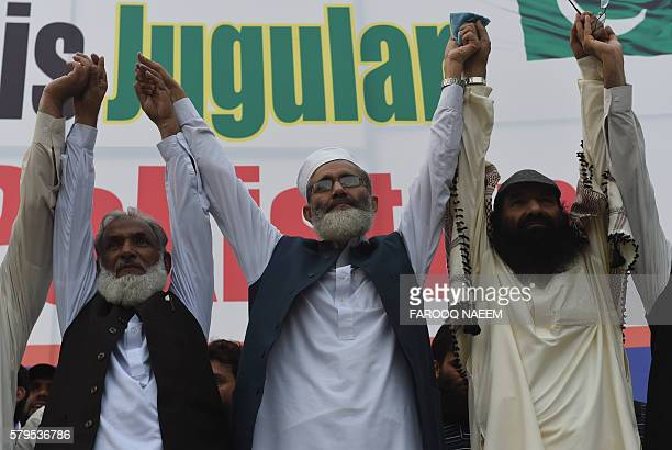 Pakistani Ameer of the Jamaat e Islami organisation Senator Sirajul Haq and Hizbul Mujahideen chief Syed Salahuddin join hands as they wave to...