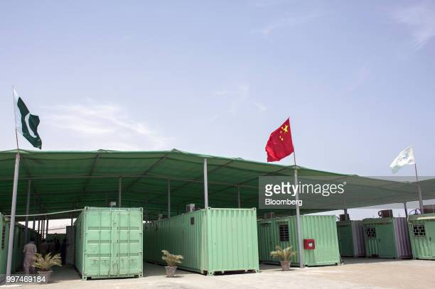 A Pakistani and Chinese national flag fly next to containers at a workers camp operated by China Overseas Ports Holding Co in Gwadar Balochistan...