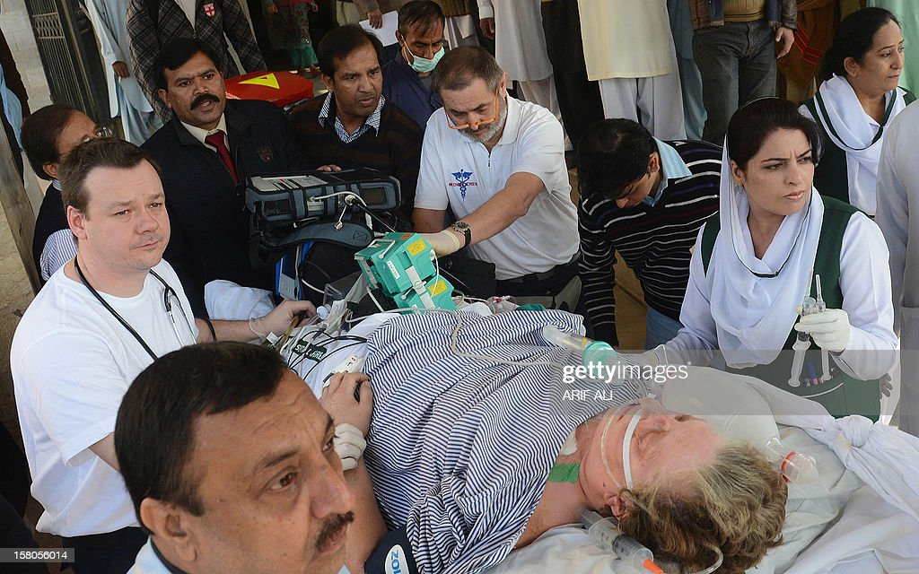 Pakistani and foreign paramedics transport injured Christian charity worker Bargetta Almby (72) on a stretcher from a hospital to an air ambulance in Lahore on December 10, 2012. A Swedish charity worker who was critically wounded in a gun attack in Pakistan last week was flown home on December 10 for specialist medical treatment, officials said. AFP PHOTO/Arif ALI
