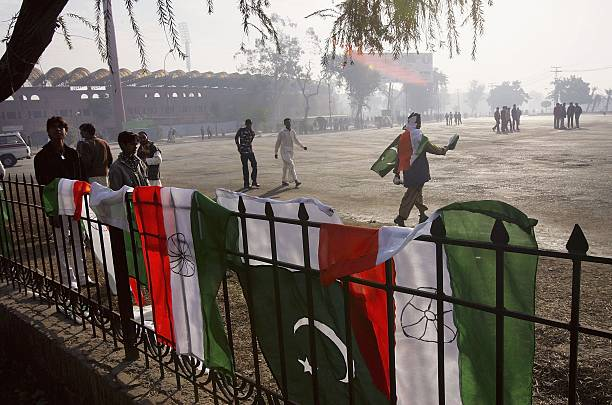Pakistani and Indian flags hang for sale in front of the Ghaddafi Cricket Stadium on the opening day of the first test match between Pakistan and...