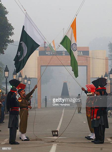 Pakistani and Indian soldiers in ceremonial garb lower their national flags at the India/Pakistan border January 4 2002 near Lahore Pakistan As...