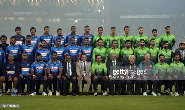 Pakistani and Sri Lankan cricketers and officials pose for a photograph before the start of the third and final Twenty20 international match at the...