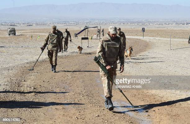Pakistani antinarcotics force personnel scan the area before the start of drugs burning ceremony in Quetta on December 12 2017 More than 45 percent...