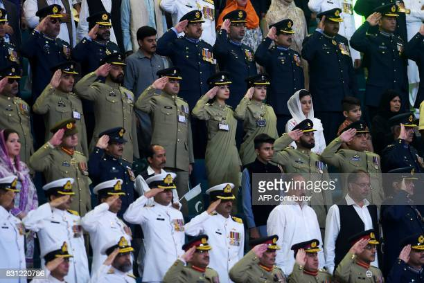 Pakistani armed forces officials salut as they listen the national anthem after hoisting the national flag during a ceremony to mark the country's...