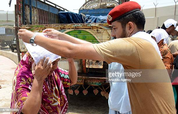 Pakistani army doctor puts a wet towel on the head of a woman to avoid heatstroke in Karachi Pakistan on June 26 2015 More than 1000 people have been...