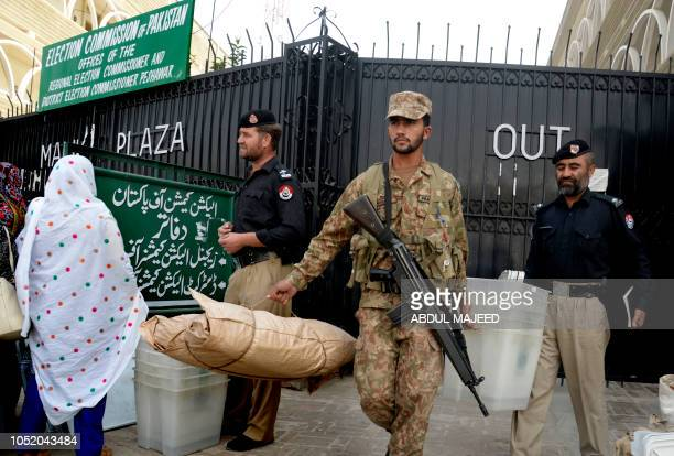A Pakistani army soldier and a policeman carry election material for a byelection after receiving them from a distributing point in Peshawar on...