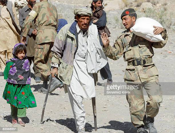 A Pakistani army soldier carries a relief supplies as he helps a disabled earthquake survivor at a hilly area of Wam one of about eight sparsely...