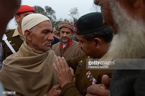 A Pakistani army soldier comforts with the father of a soldier who was shot dead along the Line of Control at a village in Bainso about 45 kms from...
